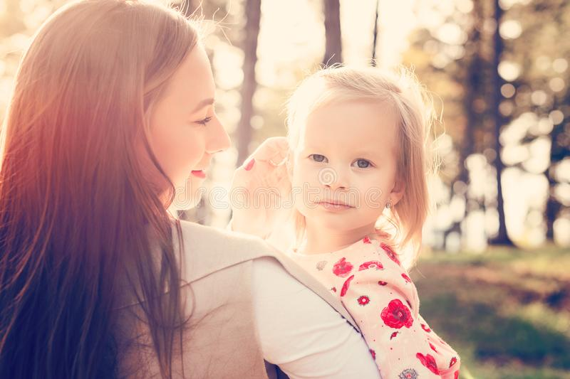 Young single mother holding cute toddler girl daughter in her arms and stroking her hair, girl power concept stock images