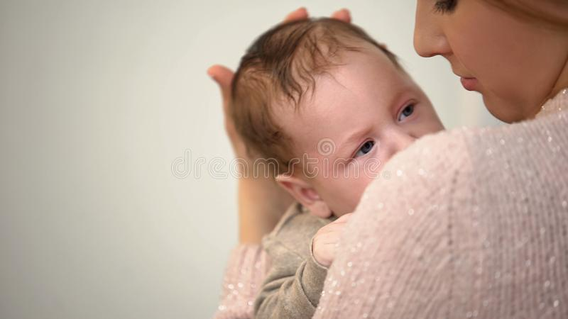 Young single mother holding newborn baby tenderly, governmental aid, support stock photography