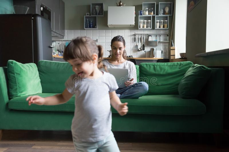Young single mother using laptop while daughter playing. Young single mother using laptop sitting on couch, sofa in living room while small preschool cute royalty free stock photos