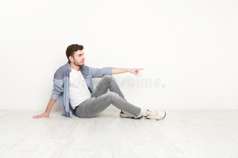 Young sitting confident man point away stock photography