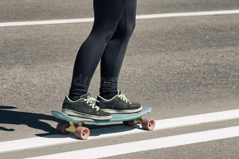 Young skateboarder girl teenager, dangerously skates on the road stock image