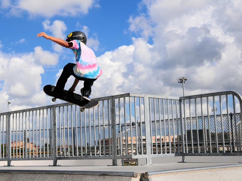 Young skateboarder hand up. Skater jumps up a ramp in city park in South Florida royalty free stock image