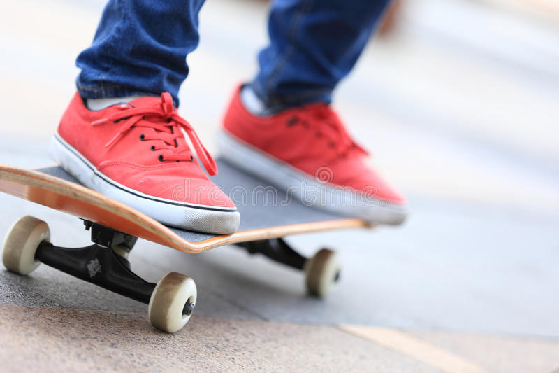 Young skateboarder legs riding on skateboard stock photos