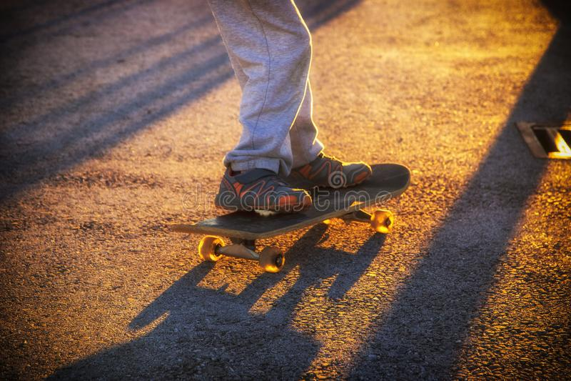 Young skateboarder legs riding skateboard at skatepark stock images