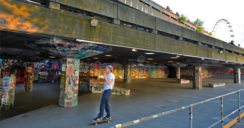 Young skateboarder in London South Bank skatepark, Undercroft. LONDON - MAY 15 2015:Young skateboarder in London South Bank skatepark, Undercroft. It's an urban stock photos