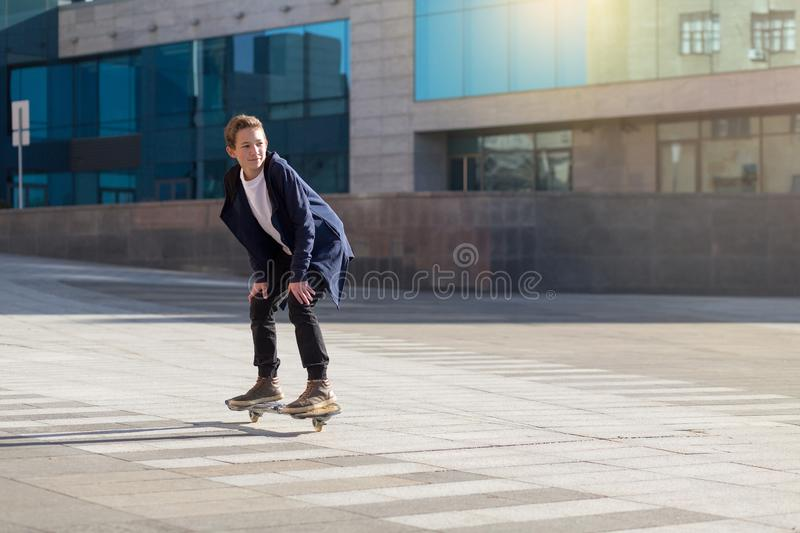 Young skateboarder on the street on a longboard moving. Young teenage skateboarder on the street on a longboard moving stock photo