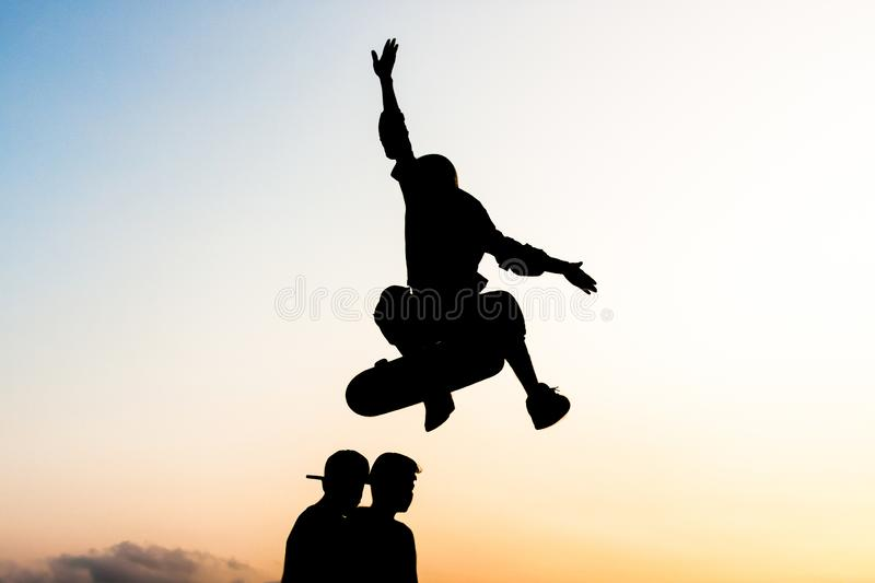 Young skateboarder trying to jump two boys with the skateboard stock photography