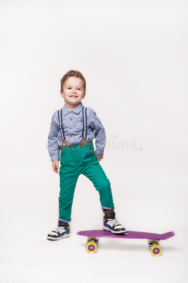 Young skater kid boy isolated on white. Full length Young skater kid boy isolated on white background. Little boy wearing stylish clothes standing on skateboard stock photos