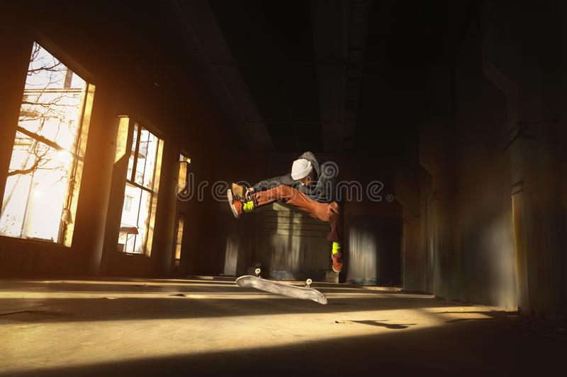 A young skater in a white hat and a black sweatshirt does a trick with a skate jump in an abandoned building in the royalty free stock photography