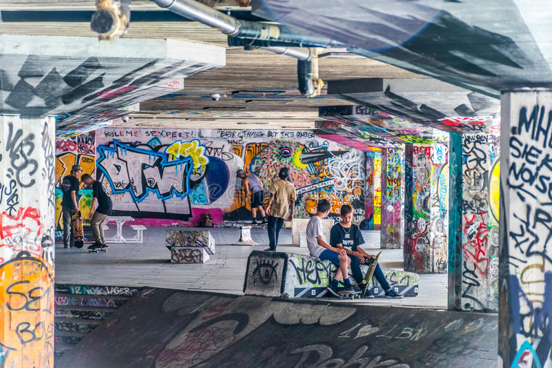 Young skaters sit amongst grafitti of Southbank skate park, London. stock images