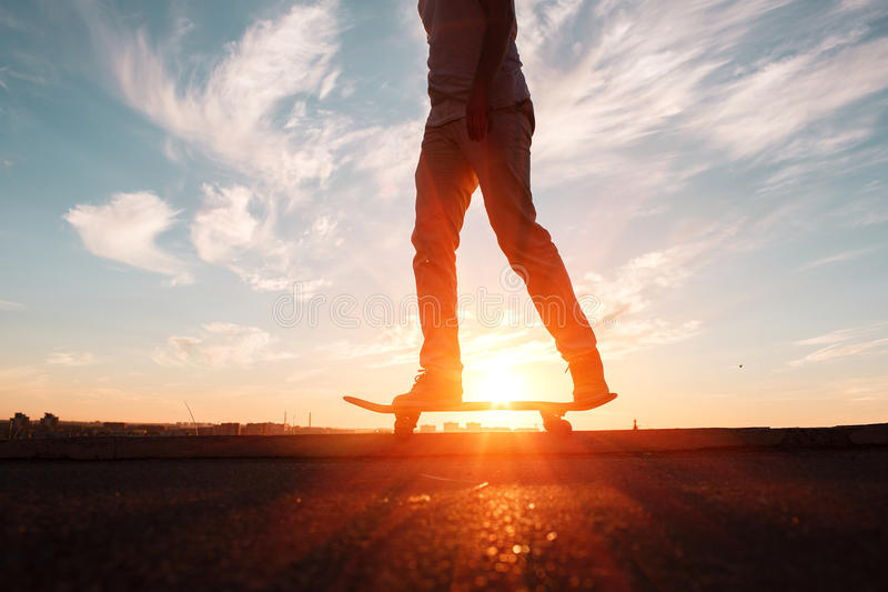 Young skaters training in the park in sunset. Birds. royalty free stock photo