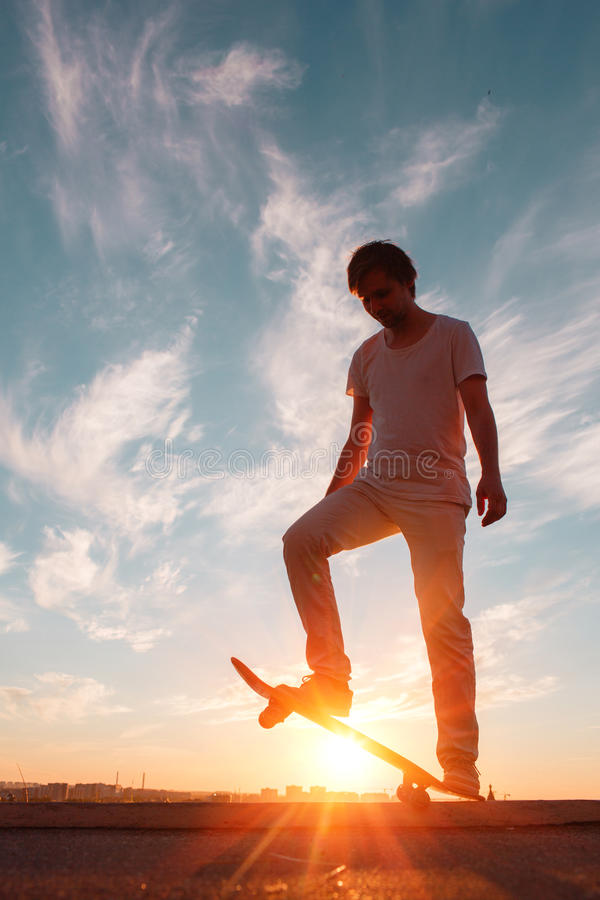 Young skaters training in the park in sunset. Birds. royalty free stock images