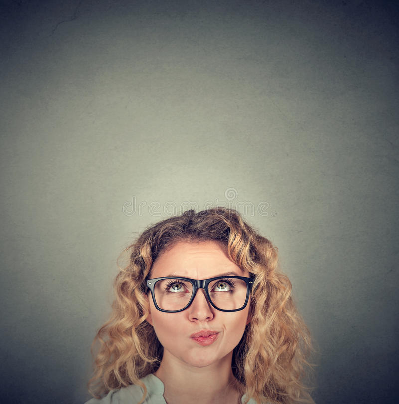 Young skeptical woman looking up stock photos