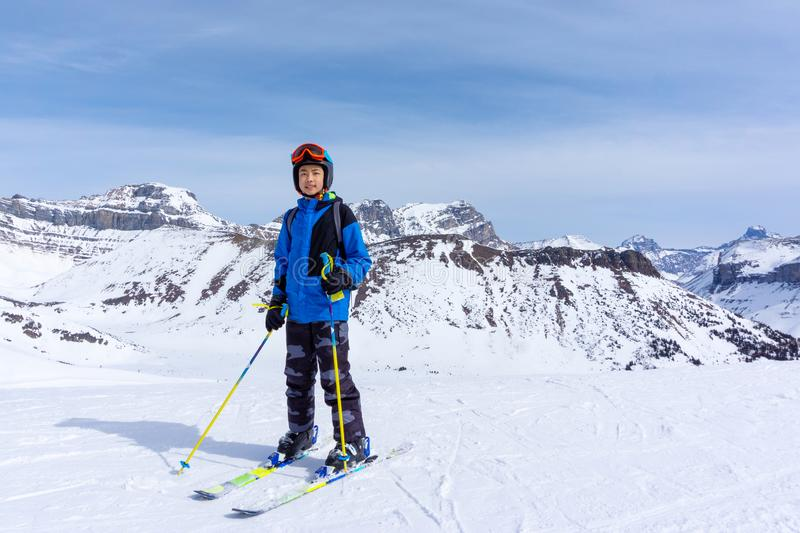 Young Skier on Mountain Edge at Lake Louise in the Canadian Rockies. Young skier standing at the edge of a mountain range in Lake Louise at the Canadian Rockies royalty free stock photo