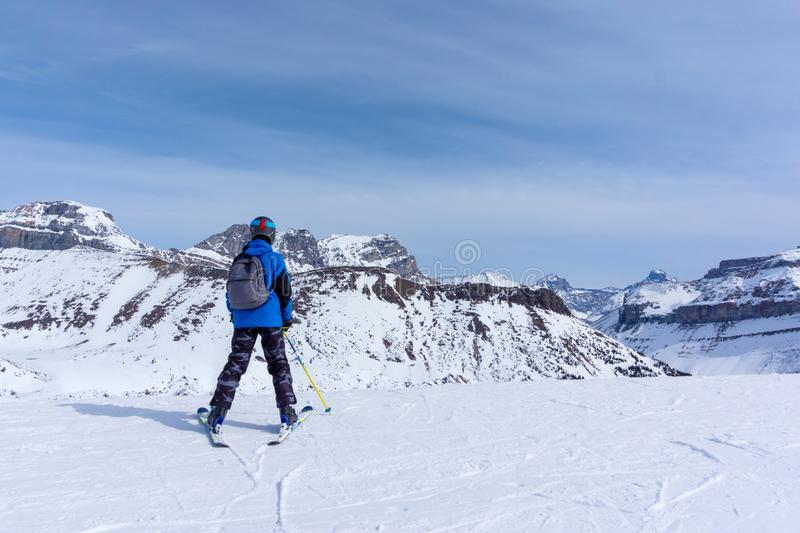 Young Skier on Mountain Edge at Lake Louise in the Canadian Rockies. Young skier standing at the edge of a mountain range in Lake Louise looking at the Canadian royalty free stock photos