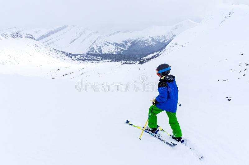 Young Skier on top of Mountain at Lake Louise in the Canadian Rockies. Young skier skiing in the backcountry of a mountain range near Lake Louise in the Canadian royalty free stock photos