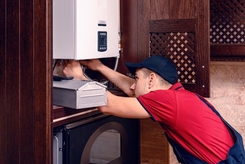 A young skilled worker regulates the gas boiler before use stock photos