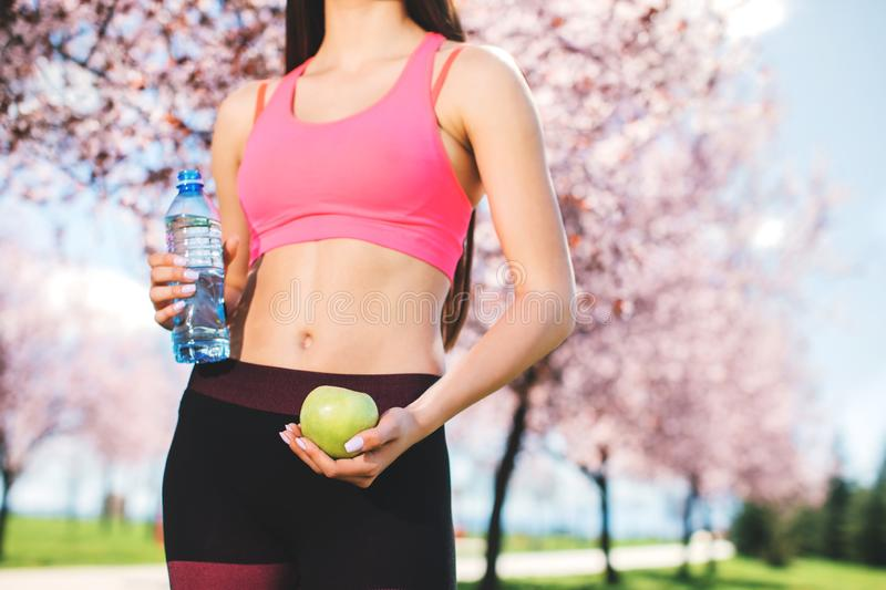 Young skinny woman holding green apple and bottle of water. Fitness and healthy lifestyle concept royalty free stock images