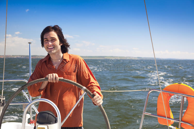 Young skipper driving sailboat stock image