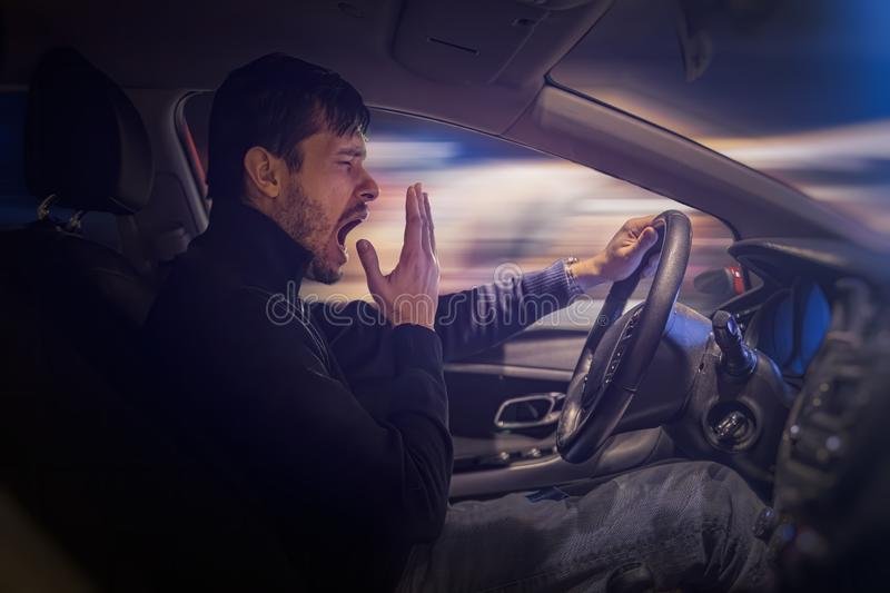 Young sleepy man is yawning and driving car at night. stock photography