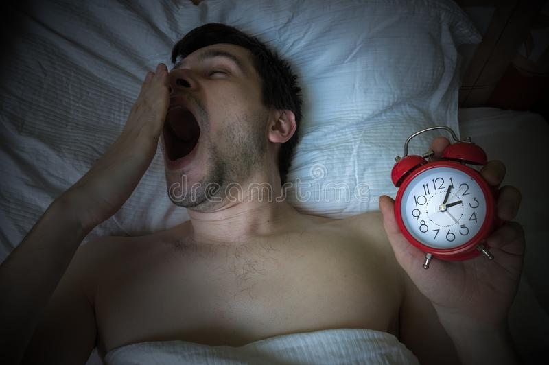 Young sleepy man is yawning and going to bed late stock photography
