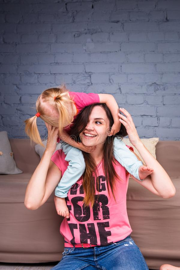 A young slender beautiful mother with her blond daughter on her shoulders play, enjoy and indulge in the teams near the sofa on th royalty free stock photography