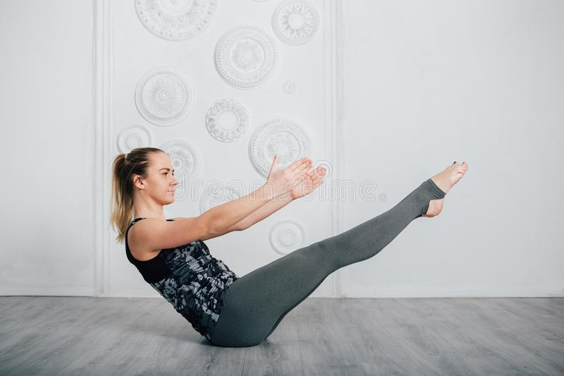 Young slender girl athlete performs fitness exercises and yoga royalty free stock photos