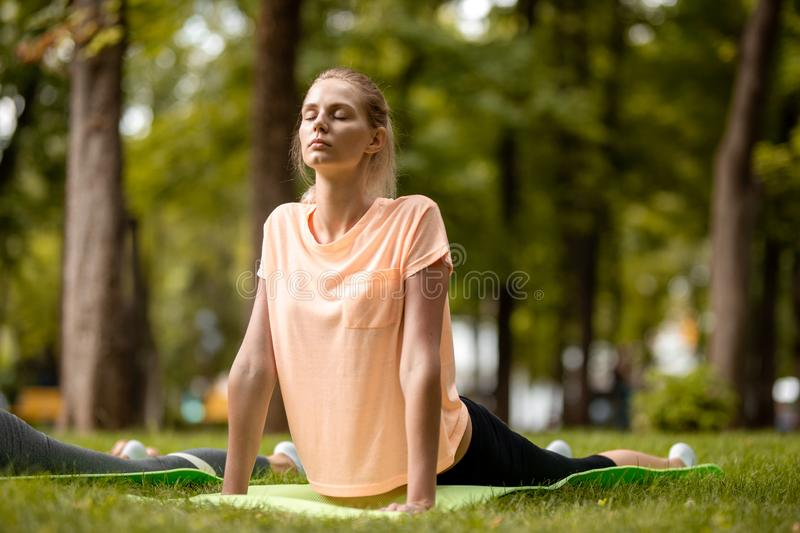 Young slender girl with closing eyes doing yoga exercises on the yoga mat on green grass in the park on a warm day. Yoga royalty free stock images