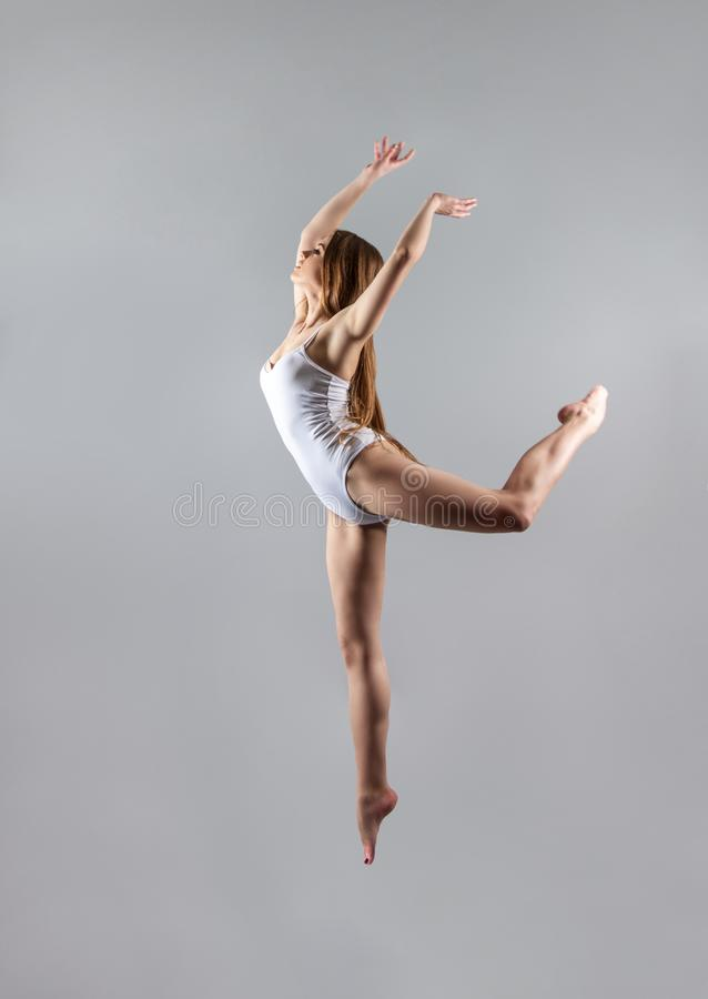 A young slender girl gymnast jumps high in the dance. royalty free stock image