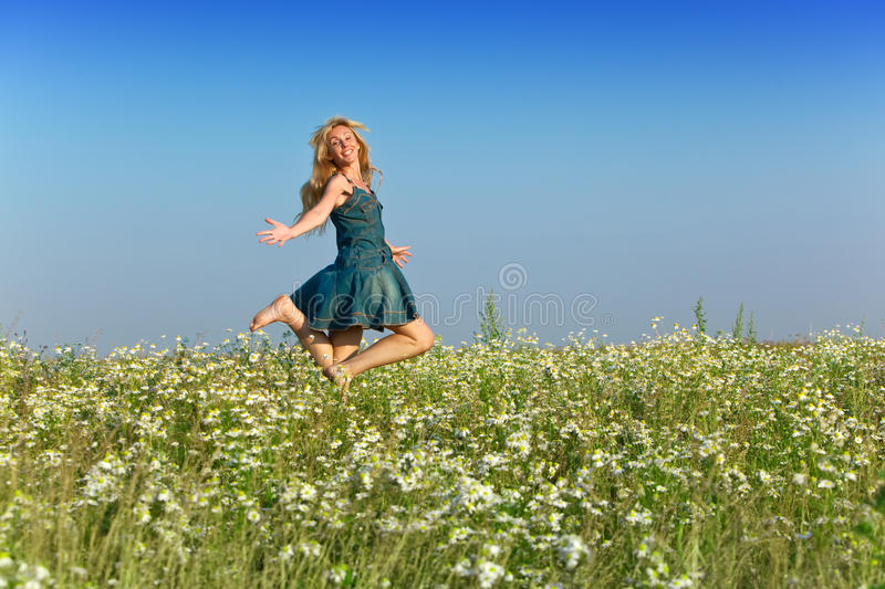 The young slender woman with a long fair hair in a blue sundress royalty free stock image