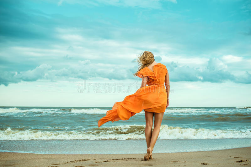 A young slender woman in orange dress is walking barefoot towards the storming sea. The train of her dress is waving. Cool wind in her hair. Outdoor shot. Copy stock photo