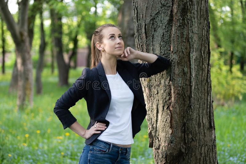 Young slender woman rests on a tree trunk, on her face is a dreamy expression royalty free stock images