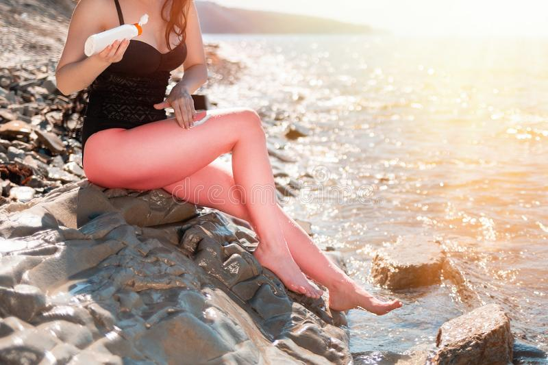 A young slender woman smears sunscreen on the beach. Redness skin on legs. The concept of protection from the sun and unwanted. Sunburn. Sunlight stock photos