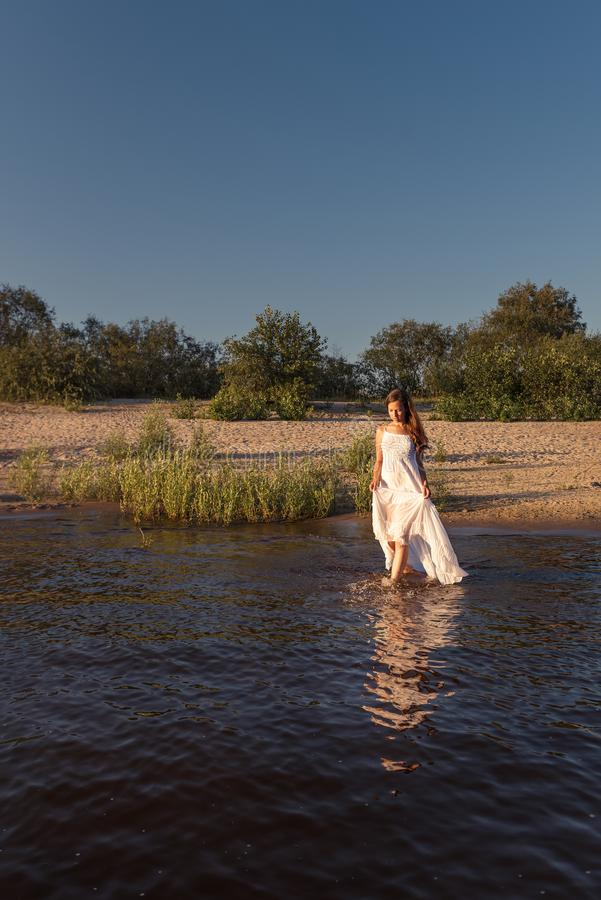 Young slender woman walks out of the beach going into the water holding a wet white summer dress exposing her legs to the knee royalty free stock photos