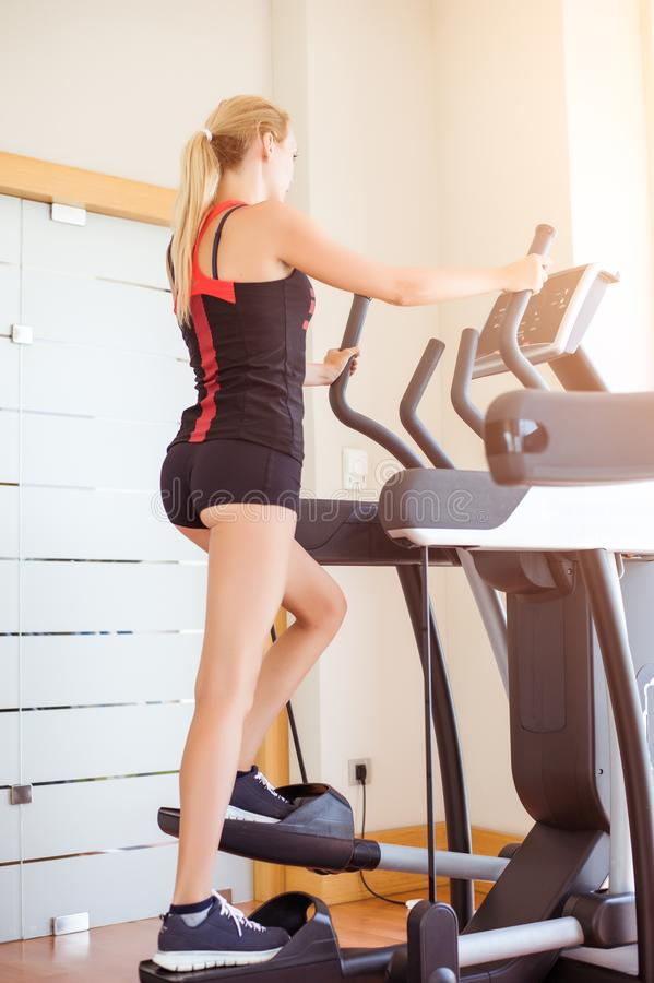 Young slim athletic girl in shorts walks in gym at the sports Elliptical trainer stock photo