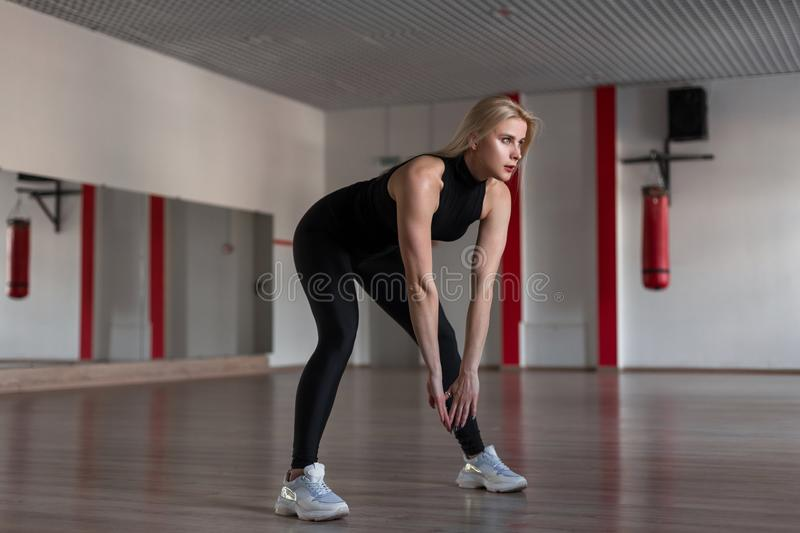Young slim athletic woman in sporty black fashionable clothes on a training in the gym. Attractive girl makes the exercises stock image
