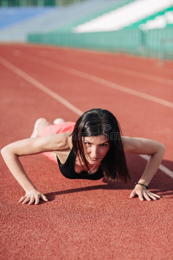 Young slim attractive brunette woman in pink shorts and black top doing plank exercise at outdoor stadium, core training and. Fitness concept, sun flare stock photo