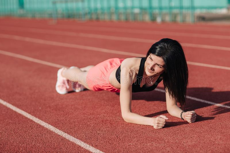 Young slim attractive brunette woman in pink shorts and black top doing plank exercise at outdoor stadium, core training and royalty free stock photos
