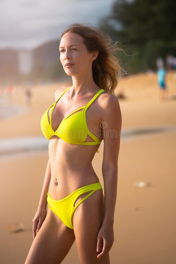 Young slim beautiful girl relaxes on the sea or ocean sandy beach stock image