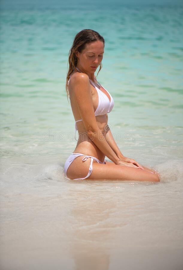 Young slim beautiful girl sits and relaxes in the sea or ocean waves stock image