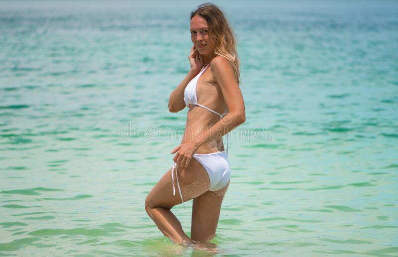 Young slim beautiful girl stay and posing in the sea or ocean waves stock photos
