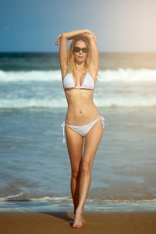 Young slim beautiful woman stay and posing in the sea or ocean waves stock image