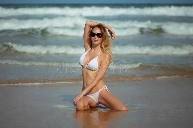 Young slim beautiful woman stay and posing in the sea or ocean waves royalty free stock images