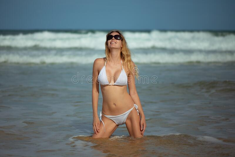 Young slim beautiful woman stay and posing in the sea or ocean waves stock images
