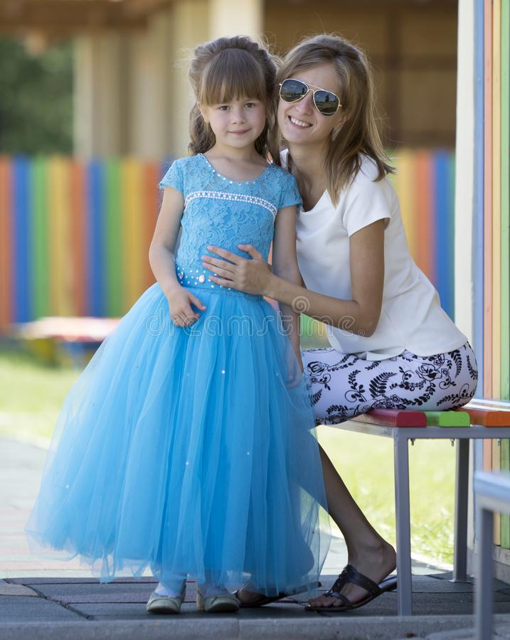 Young slim blond smiling mother, aunt or sister hugs small pretty preschool daughter girl in long nice blue evening dress on stock photo