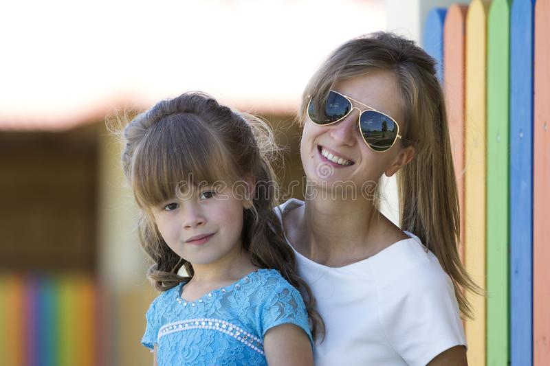 Young slim blond smiling mother, aunt or sister hugs small pretty preschool daughter girl in nice blue dress on blurred colorful p stock photography