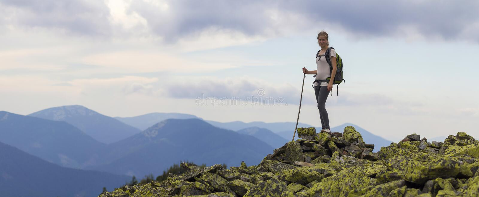 Young slim blond tourist girl with backpack and stick standing on rocky top against bright blue morning sky on foggy mountain rang royalty free stock image