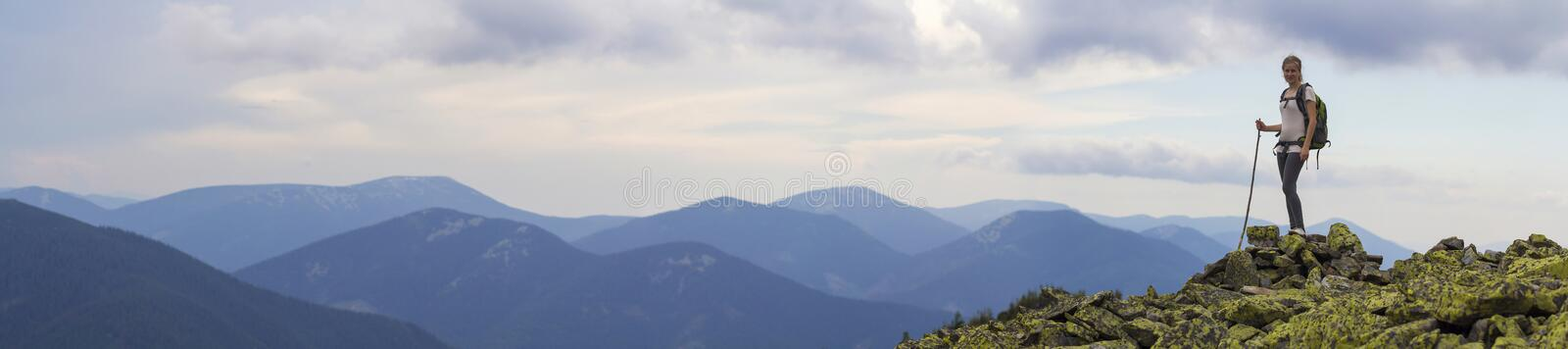 Young slim blond tourist girl with backpack and stick standing on rocky top against bright blue morning sky on foggy mountain stock photos