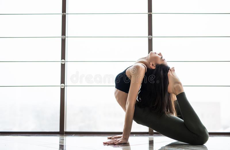 Young slim blond woman in yoga class making beautiful asana exercises. royalty free stock photos