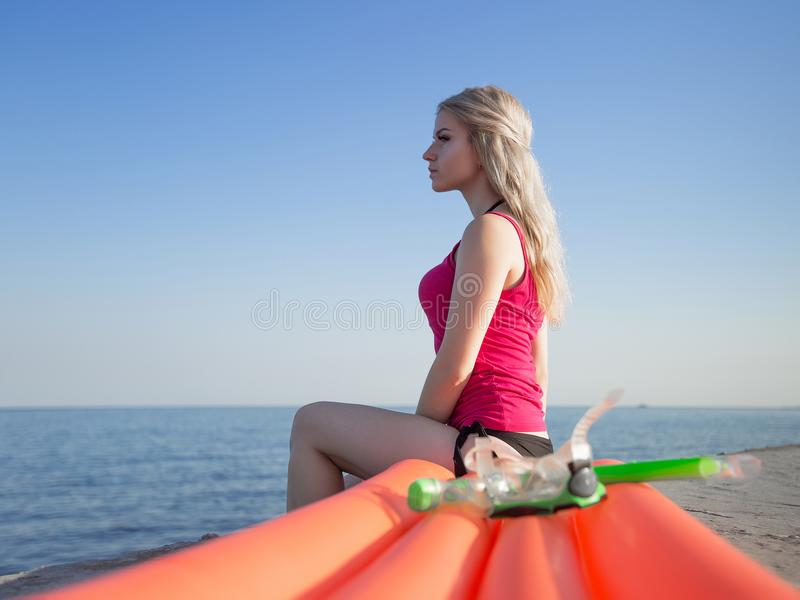 Young slim blonde girl in pink tank top at sea. Young slim blonde woman in pink tank top and black lower part of bikini sits on pool raft and looks away. Blonde royalty free stock photography